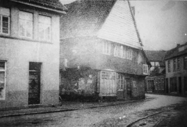 """-97- Ende der Häuserzeile zwischen Burgstrße und Lange Straße auf der Südseite - Am Markt 23, der Durchgang zwischen den beiden Häusern Fleischerei Krümpelbeck (links) und dem Lebensmittelgeschäft """"von Schemde"""" ´von der Kirche zum Markt. Aufnahme um 1938"""