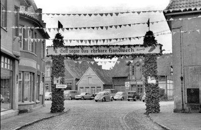 """-1- Hier beginnt die Straße Am Markt, Anlass war der Kolpingtag 1952. Auf der linken Seite sieht man zuerst noch eine Ecke von Bahlmann Damenbekleidung, daneben die Gastwirtschaft """"Horns Pietze"""", heute zu Optik Weiss gehörend."""