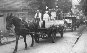 -56- Dieser schon oben gezeigte Umzug zum 1. Mai 1934 führt hier gerade am Haus Kröger vorbei. Der Fahrer des Fuhrwerks ist A. Völker.