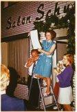 -24c- Salon Schumacher, Dielmanns (Maohlers) Gertrud auf der Leiter