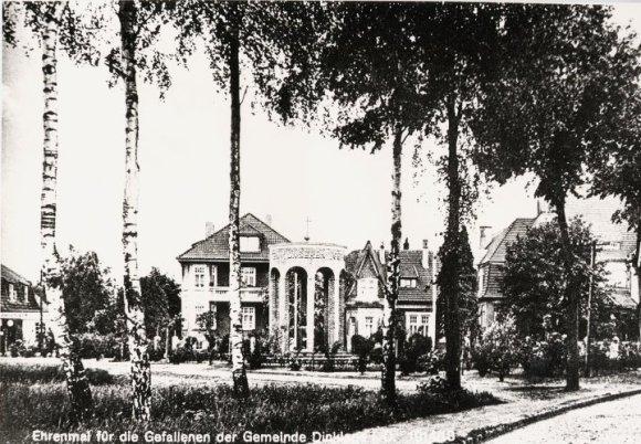 -68- Denkmal für die Toten der Kriege mit Durchblick auf die Häuser (v.l.n.r.) Calvelage, Dünnebacke, Evers, Holthaus