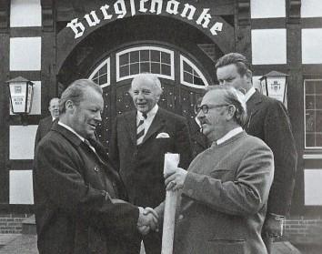 """1973 Der Bundeskanzler Willy Brand besucht Dinklage. und tagt mit Teilen seines Kabinetts im Burghotel. DEr SPD MdB Hans """"lumpi"""" Lemp aus Vechta überreicht einen Räucheraal als Geschenk. Im Hintergrund Walter Scheel"""